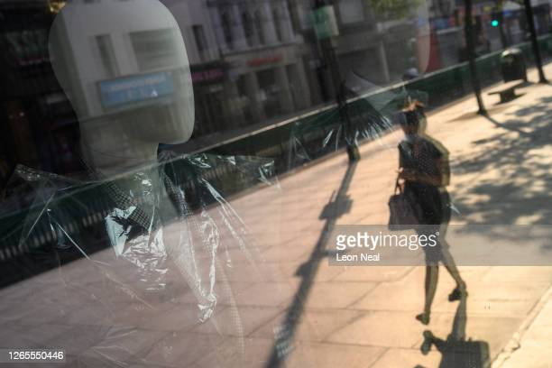Mannequins wrapped in protective plastic are seen in the window of a closed clothing store on August 12, 2020 in London, United Kingdom. The Office...