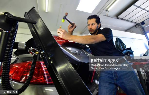 Manny Aguirre owner of Boulder Dents works to remove dents caused by hail at the shop in Boulder on Thursday August 9 2018