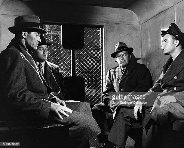 Manny Balestrero far left sits in the back of a police van with detectives in a scene from the 1956 Alfred Hitchcock film The Wrong Man