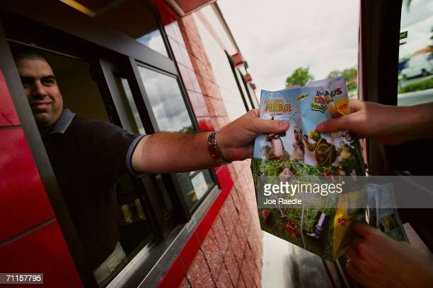 Manny Barnet Wendy's district manager hands customer an order from the drivethrough window June 8 2006 in Miami Florida In a move that significantly...