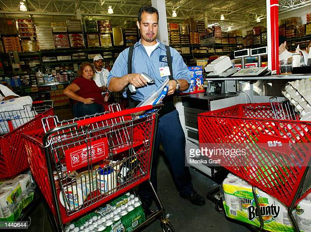 Manny Cruz scans items in the checkout line at BJ's Warehouse where he works October 1 2002 at the Gateway Center in Brooklyn New York during the...