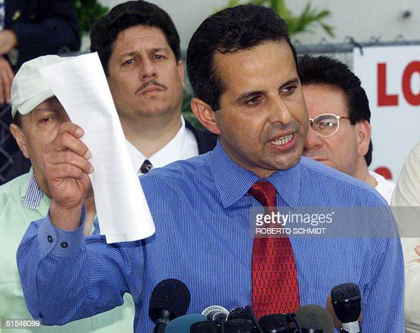 Manny Diaz an attorney of the Elian Gonzalez's Miami relatives shows legal documents during a press conference in front of their home in Little...