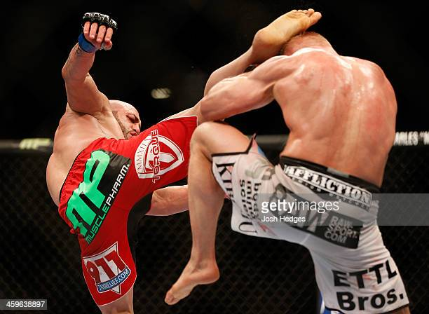 Manny Gamburyan kicks Dennis Siver in their featherweight bout during the UFC 168 event at the MGM Grand Garden Arena on December 28 2013 in Las...