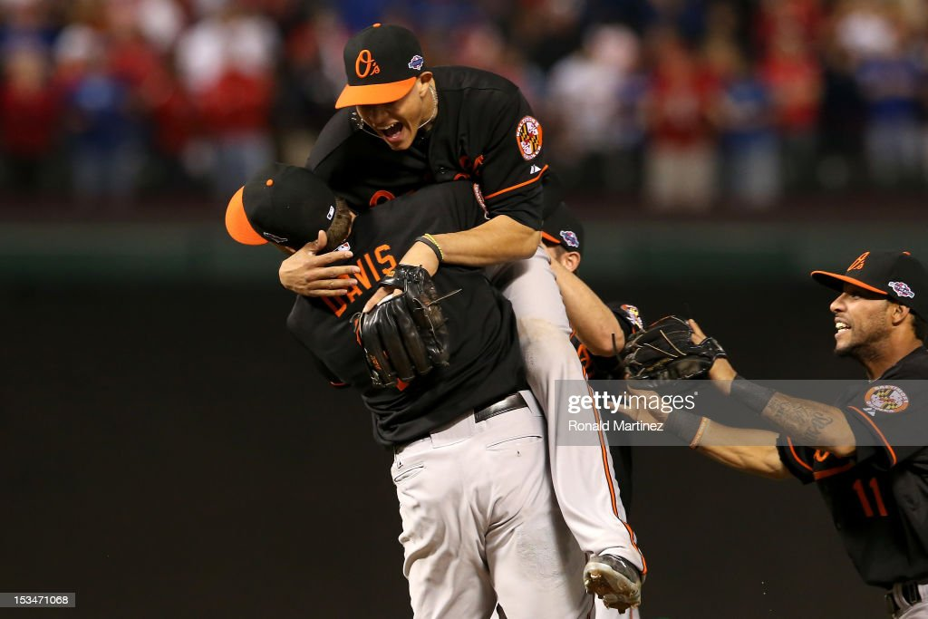 Manny Machado (C) #13 and Chris Davis (L) #19 of the Baltimore Orioles celebrate after they won 5-1 against the Texas Rangers during the American League Wild Card playoff game at Rangers Ballpark in Arlington on October 5, 2012 in Arlington, Texas.
