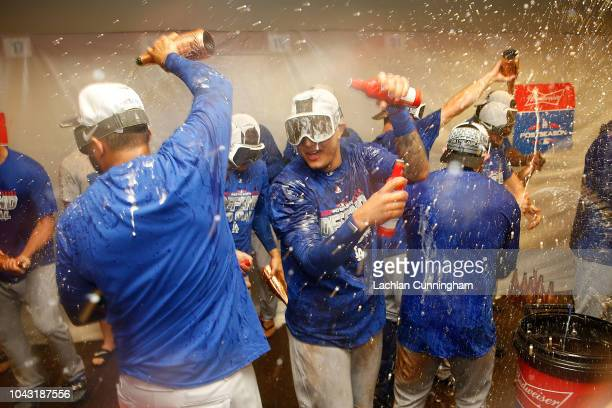 Manny Machado of the Los Angeles Dodgers celebrates with teammates after the Dodgers clinched a postseason spot by defeating the San Francisco Giants...