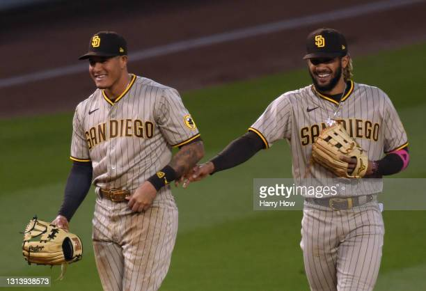 Manny Machado and Fernando Tatis Jr. #23 of the San Diego Padres laugh after a defensive play by Machado for an out of Austin Barnes of the Los...