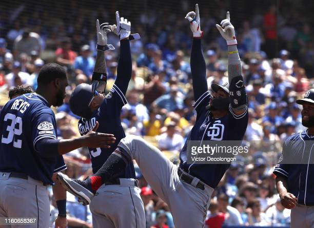 Manny Machado and Fernando Tatis Jr #23 of the San Diego Padres celebrate Tatis Jr's threerun home run near the dugout as teammates Franmil Reyes and...