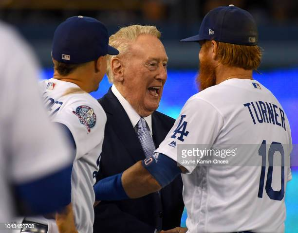Manny Machado and Justin Turner of the Los Angeles Dodgers talks with retired broadcaster Vin Scully who was attending a pregame ceremony honoring...