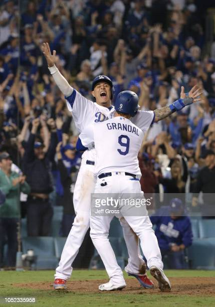Manny Machado and Yasmani Grandal of the Los Angeles Dodgers celebrate after Machado scored the winning run in the 13th inning of Game Four of the...