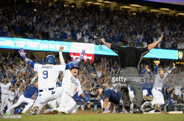 Manny Machado and Yasmani Grandal of the Los Angeles Dodgers celebrate after Machado scored the winning run as catcher Erik Kratz of the Milwaukee...