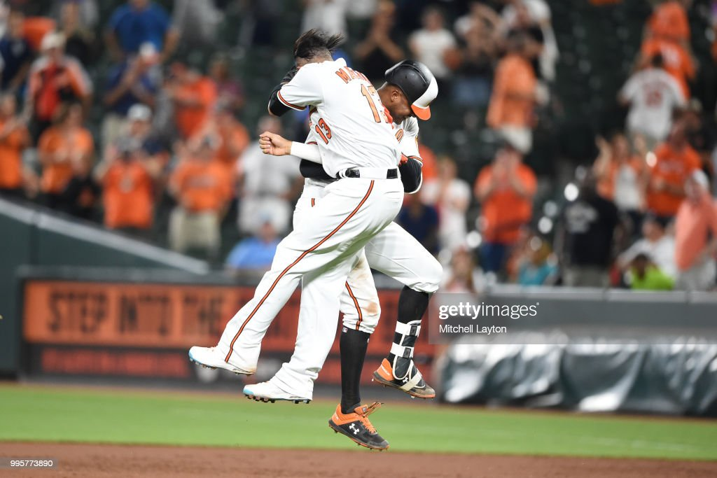 Manny Machado #13 celebrates with Jonathan Schoop #6 on his walk off hit in the ninth inning during a baseball game against the New York Yankees at Oriole Park at Camden Yards on July 10, 2018 in Baltimore, Maryland.