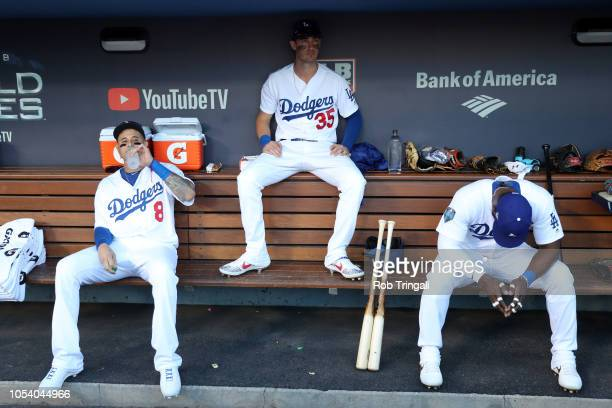 Manny Machado Cody Bellinger and Yasiel Puig of the Los Angeles Dodgers get ready in the dugout prior to Game 3 of the 2018 World Series against the...