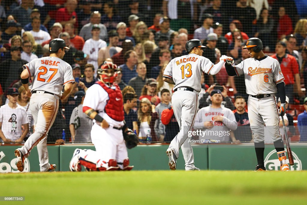 Manny Machado #13 high fives Jonathan Schoop #6 of the Baltimore Orioles after hitting a two-run home run in the ninth inning of a game against the Boston Red Sox at Fenway Park on May 17, 2018 in Boston, Massachusetts.