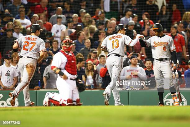 Manny Machado high fives Jonathan Schoop of the Baltimore Orioles after hitting a tworun home run in the ninth inning of a game against the Boston...