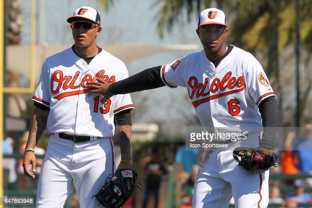 Manny Machado is pushed away by Jonathan Schoop of the Orioles for the warm up tossed ball from first baseman Chris Davis during the spring training...