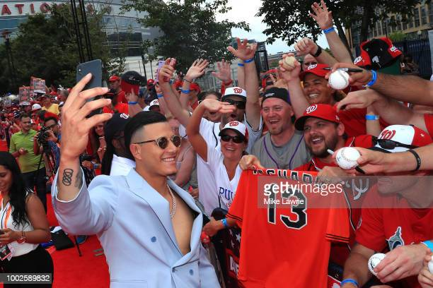 Manny Machado of the Baltimore Orioles and the American interacts with fans at the 89th MLB AllStar Game presented by MasterCard red carpet at...