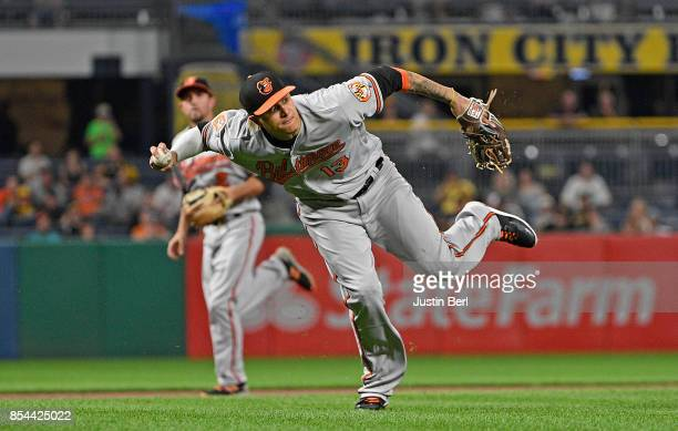 Manny Machado of the Baltimore Orioles attempts a throw to first base but cannot get a force out of David Freese of the Pittsburgh Pirates in the...