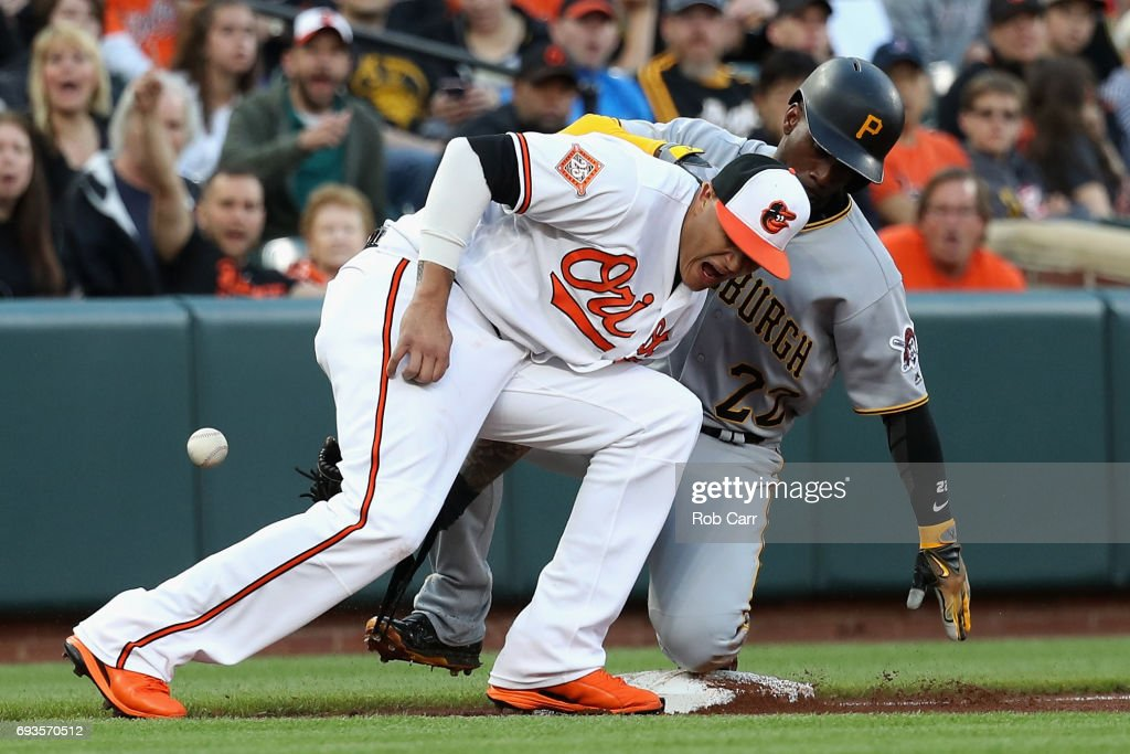 Manny Machado #13 of the Baltimore Orioles bobbles the the throw as Andrew McCutchen #22 of the Pittsburgh Pirates safely steals third base in the second inning at Oriole Park at Camden Yards on June 7, 2017 in Baltimore, Maryland.