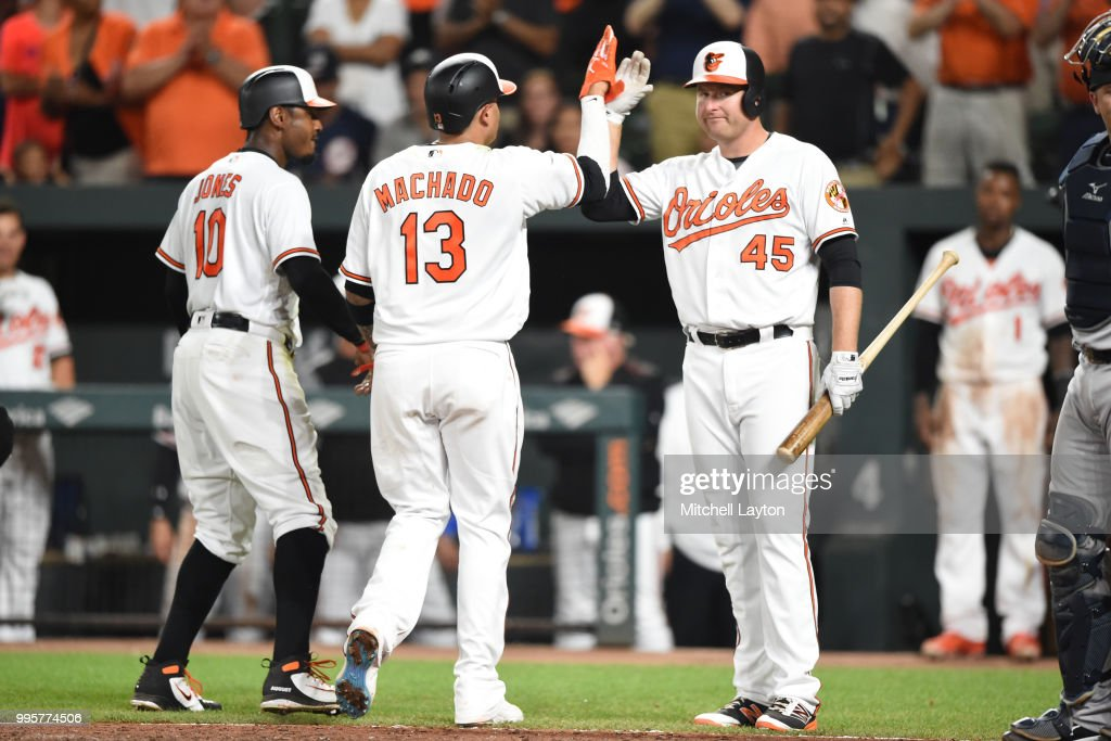 Manny Machado #13 of the Baltimore Orioles celebrates a two run home run in the seventh inning with Adam Jones #10 and Mark Turmbo #45 during a baseball game against the New York Yankees at Oriole Park at Camden Yards on July 10, 2018 in Baltimore, Maryland.
