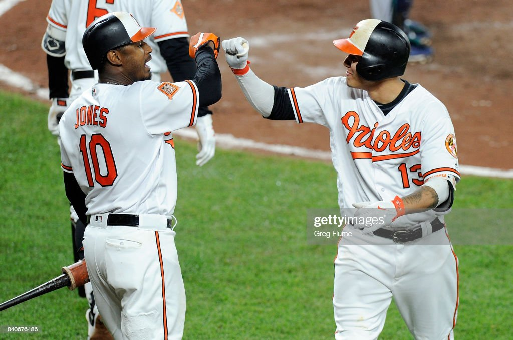 Manny Machado #13 of the Baltimore Orioles celebrates with Adam Jones #10 after hitting a home run in the sixth inning against the Seattle Mariners at Oriole Park at Camden Yards on August 29, 2017 in Baltimore, Maryland.