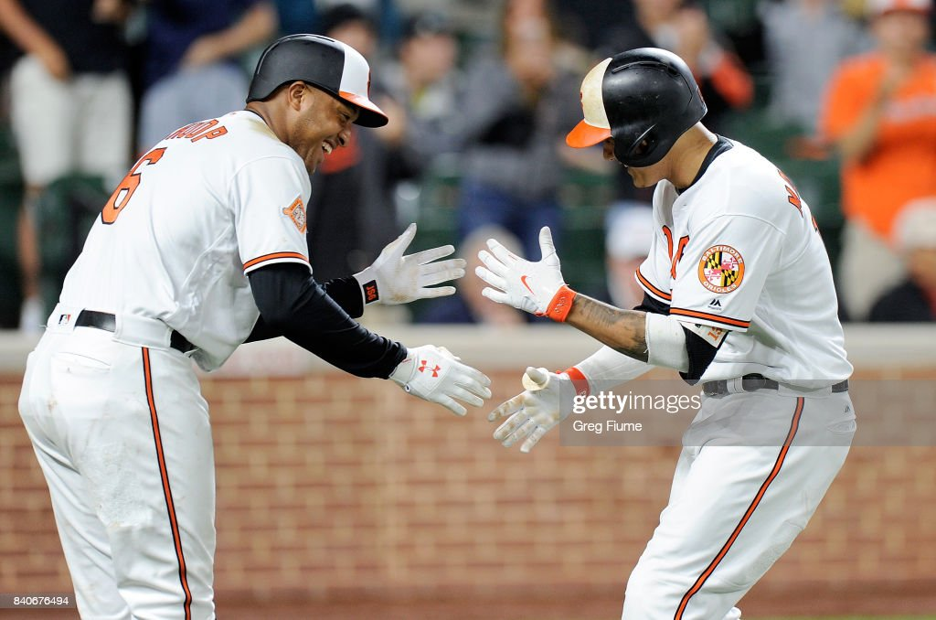 Manny Machado #13 of the Baltimore Orioles celebrates with Jonathan Schoop #6 after hitting a home run in the eighth inning against the Seattle Mariners at Oriole Park at Camden Yards on August 29, 2017 in Baltimore, Maryland.