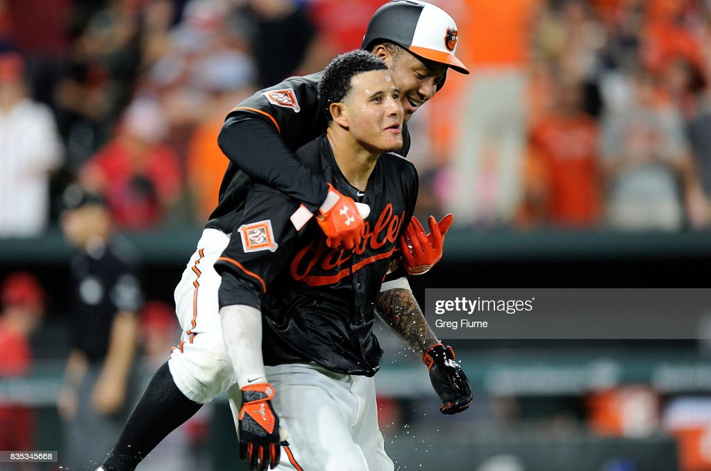 Manny Machado #13 of the Baltimore Orioles celebrates with Jonathan Schoop #6 after hitting the game winning grand slam in the ninth inning against the Los Angeles Angels at Oriole Park at Camden Yards on August 18, 2017 in Baltimore, Maryland. Baltimore won the game 9-7.