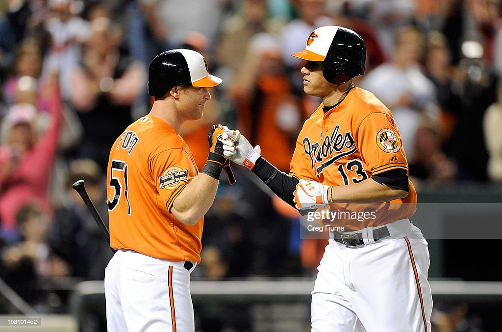 Manny Machado #13 of the Baltimore Orioles celebrates with Lew Ford #51 after hitting a home run in the seventh inning against the Boston Red Sox at Oriole Park at Camden Yards on September 29, 2012 in Baltimore, Maryland. Baltimore won the game 4-3.