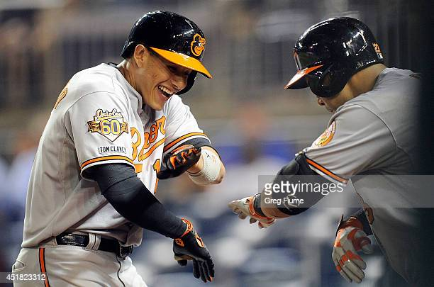 Manny Machado of the Baltimore Orioles celebrates with Nelson Cruz after hitting a home run in the eleventh inning against the Washington Nationals...