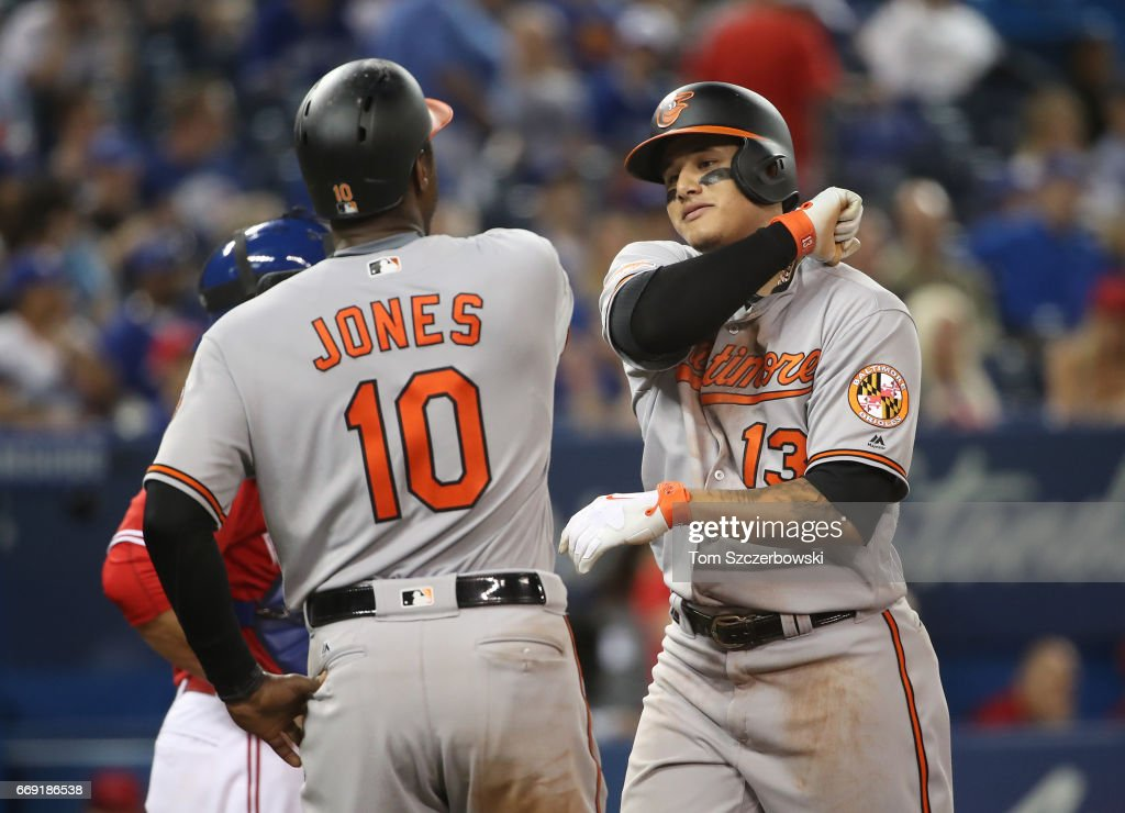Manny Machado #13 of the Baltimore Orioles is congratulated by Adam Jones #10 after hitting a two-run home run in the eighth inning during MLB game action against the Toronto Blue Jays at Rogers Centre on April 16, 2017 in Toronto, Canada.