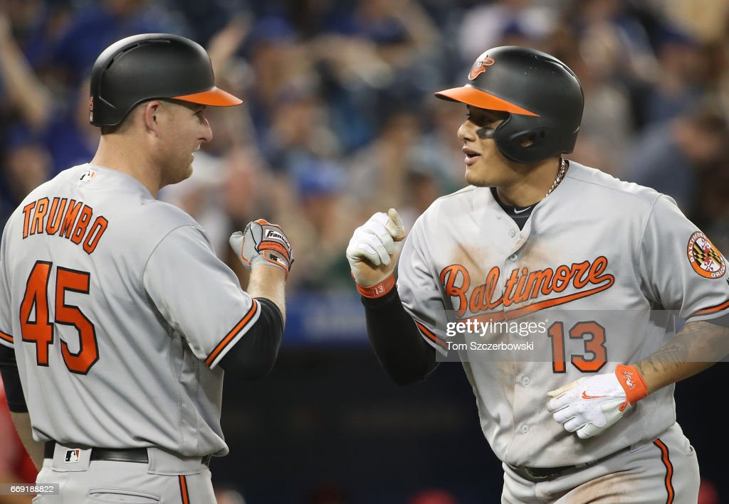 Manny Machado #13 of the Baltimore Orioles is congratulated by Mark Trumbo #45 after hitting a two-run home run in the eighth inning during MLB game action against the Toronto Blue Jays at Rogers Centre on April 16, 2017 in Toronto, Canada.