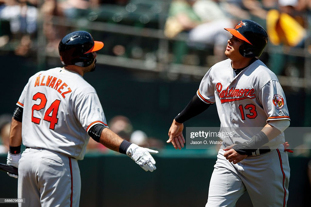 Manny Machado #13 of the Baltimore Orioles is congratulated by Pedro Alvarez #24 after scoring a run against the Oakland Athletics during the fourth inning at the Oakland Coliseum on August 11, 2016 in Oakland, California. The Baltimore Orioles defeated the Oakland Athletics 9-6.