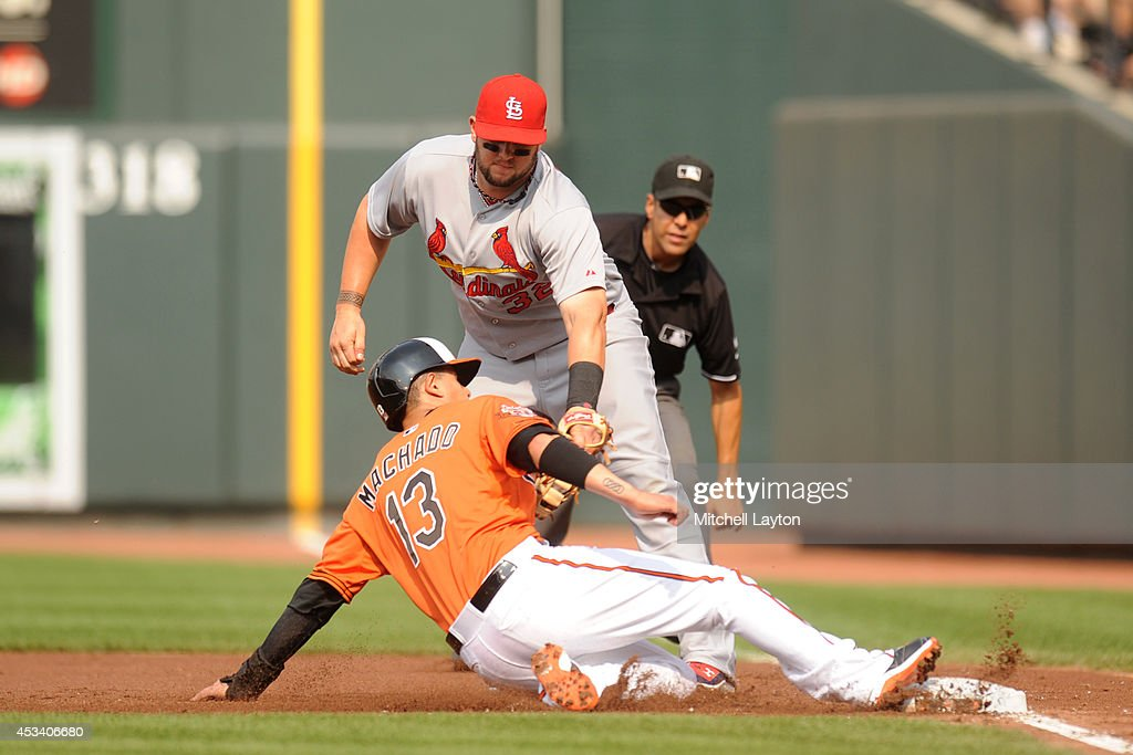 Manny Machado #13 of the Baltimore Orioles is doubled up by Matt Adams #32 of the St. Louis Cardinals up on line drive hit by Adam Jones #10 (not pictured) in the first inning during a baseball game on August 9, 2014 at Oriole Park at Camden Yards in Baltimore, Maryland. The Orioles won 10-3.