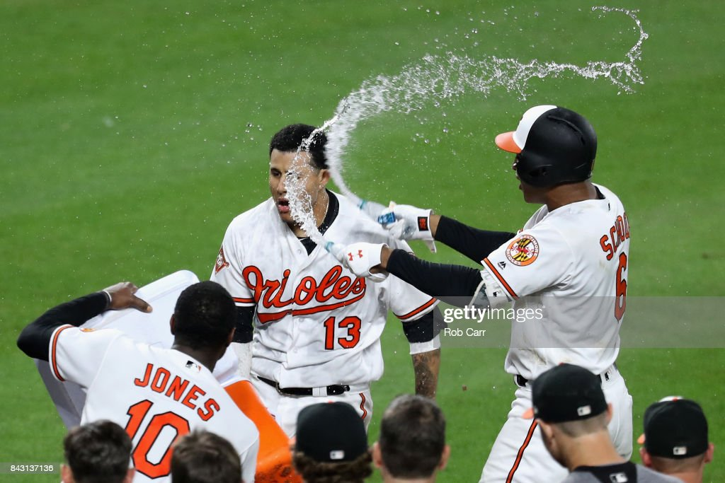 Manny Machado #13 of the Baltimore Orioles is doused with water by Adam Jones #10 and Jonathan Schoop #6 after hitting a two RBI walk off home run to give the Orioles a 7-6 win over the New York Yankees at Oriole Park at Camden Yards on September 5, 2017 in Baltimore, Maryland.