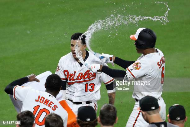 Manny Machado of the Baltimore Orioles is doused with water by Adam Jones and Jonathan Schoop after hitting a two RBI walk off home run to give the...