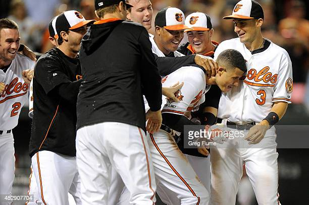 Manny Machado of the Baltimore Orioles is mobbed by teammates after hitting the game winning home run in the 12th inning against the Los Angeles...