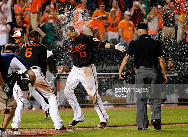 Manny Machado of the Baltimore Orioles is sprayed with water by teammate Jonathan Schoop after hitting a two RBI walk off home run against the...