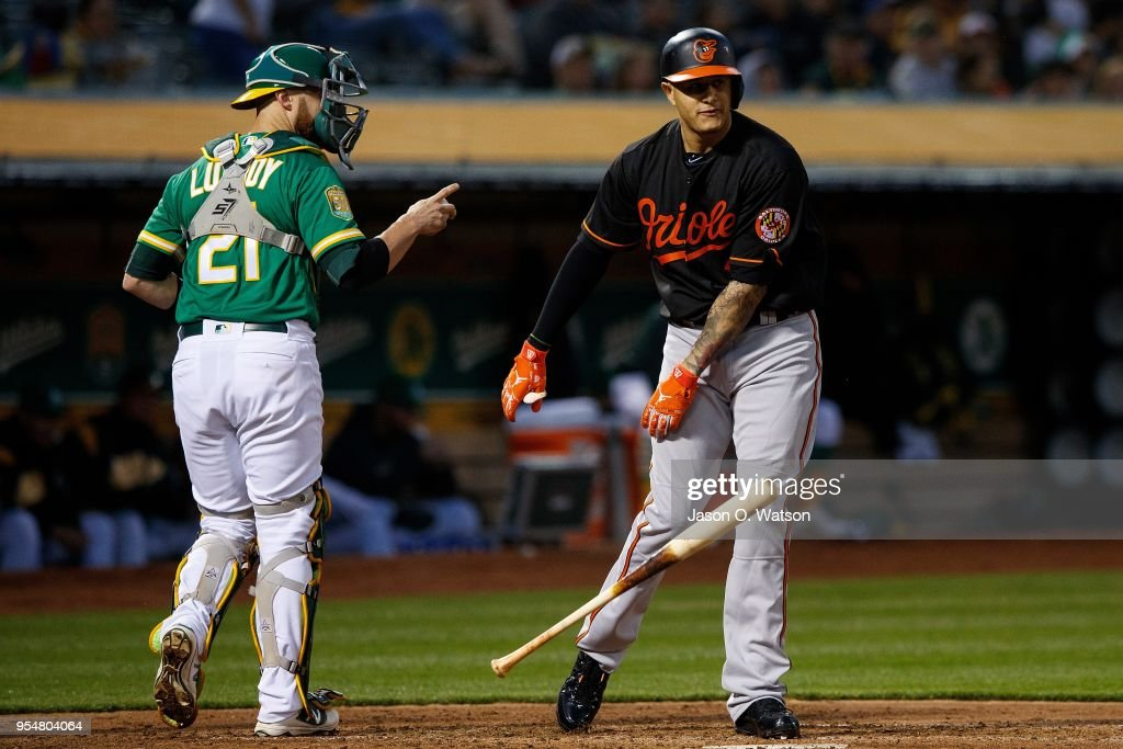 Manny Machado #13 of the Baltimore Orioles reacts after striking out in front of Jonathan Lucroy #21 of the Oakland Athletics during the third inning at the Oakland Coliseum on May 4, 2018 in Oakland, California. The Oakland Athletics defeated the Baltimore Orioles 6-4.