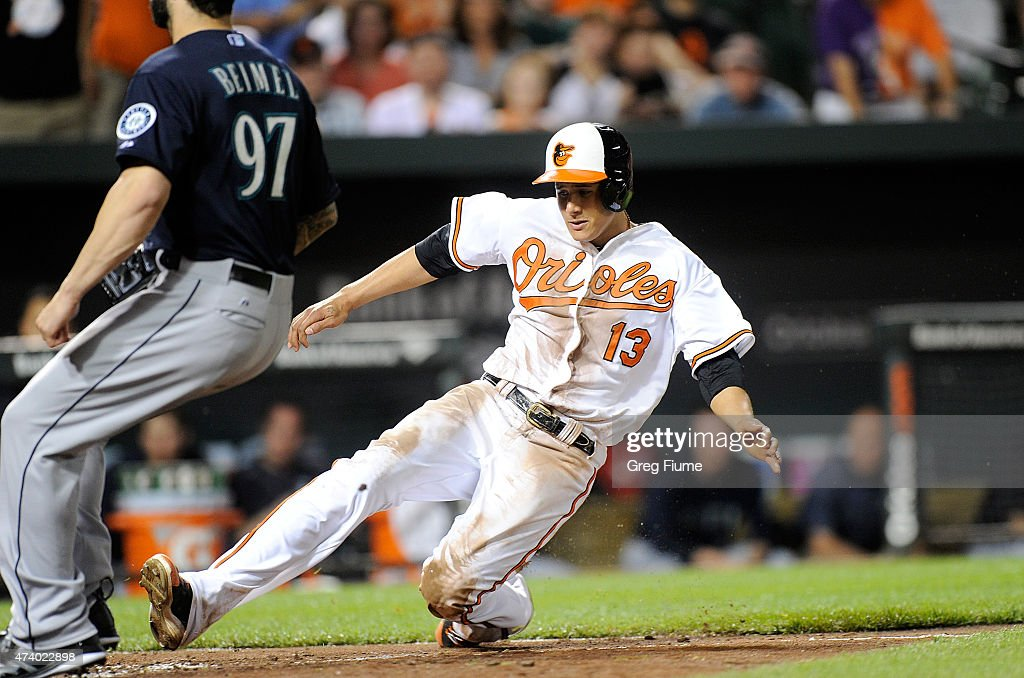 Manny Machado #13 of the Baltimore Orioles scores on a passed ball in the eighth inning against the Seattle Mariners at Oriole Park at Camden Yards on May 19, 2015 in Baltimore, Maryland.