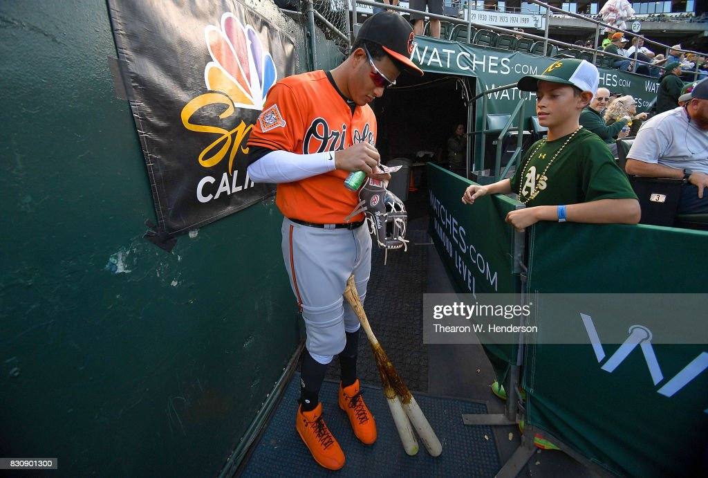 Manny Machado #13 of the Baltimore Orioles signs his Topps trading card for a fan prior to the start of their game against the Oakland Athletics at Oakland Alameda Coliseum on August 12, 2017 in Oakland, California.
