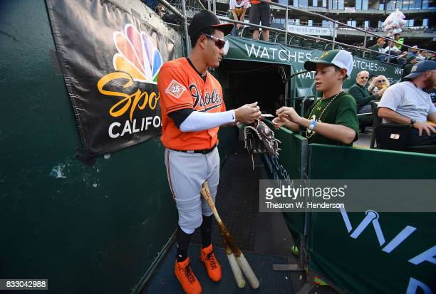 Manny Machado of the Baltimore Orioles signs his Topps trading card for a fan prior to the start of their game against the Oakland Athletics at...