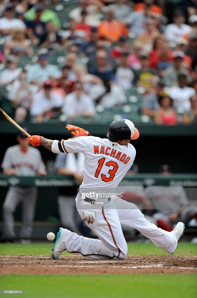 Manny Machado #13 of the Baltimore Orioles slips on a swinging strike in the sixth inning against the Boston Red Sox at Oriole Park at Camden Yards on June 13, 2018 in Baltimore, Maryland.