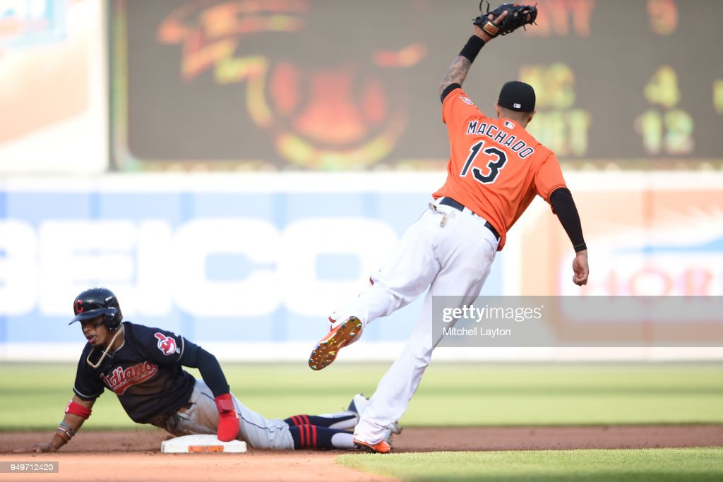 Manny Machado #13 of the Baltimore Orioles tags out Francisco Lindor #12 of the Cleveland Indians trying to steal second base in the seventh inning during a baseball game against the Cleveland Indians at Oriole Park at Camden Yards on April 21, 2018 in Baltimore, Maryland.
