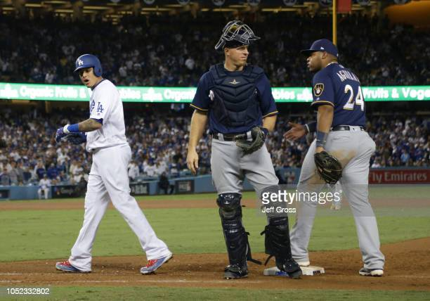 Manny Machado of the Los Angeles Dodgers and Jesus Aguilar of the Milwaukee Brewers exchange words after Machado's foot hit Aguilar's on his way to...