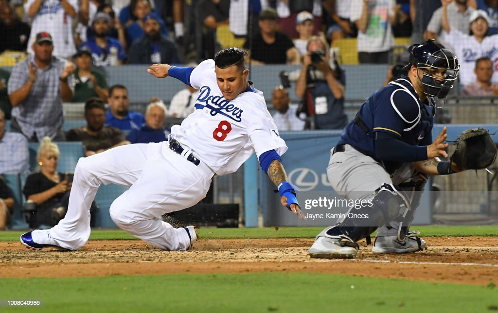 Manny Machado #8 of the Los Angeles Dodgers beats the throw to Manny Pina #9 of the Milwaukee Brewers as he scores a run on a triple by Max Muncy #13 of the Los Angeles Dodgers in the third inning at Dodger Stadium on July 30, 2018 in Los Angeles, California.