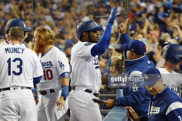 Manny Machado of the Los Angeles Dodgers celebrates with manager Dave Roberts and teammates just outside the dugout after Puig hit a threerun home...