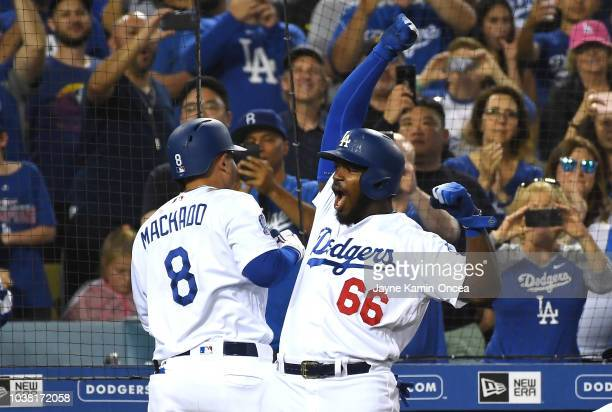 Manny Machado of the Los Angeles Dodgers celebrates with teammate Yasiel Puig after hitting a threerun home run in the third inning against the San...