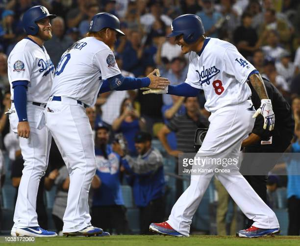 Manny Machado of the Los Angeles Dodgers celebrates with teammates Justin Turner and Max Muncy after hitting a threerun home run in the third inning...
