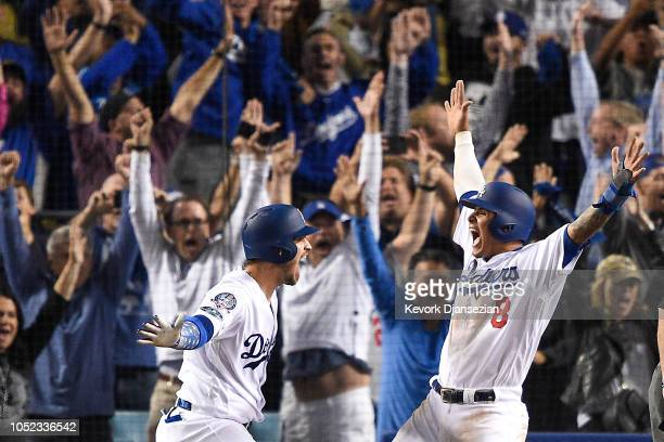 Manny Machado of the Los Angeles Dodgers celebrates with Yasmani Grandal after scoring on a walkoff single by Cody Bellinger to win Game Four of the...