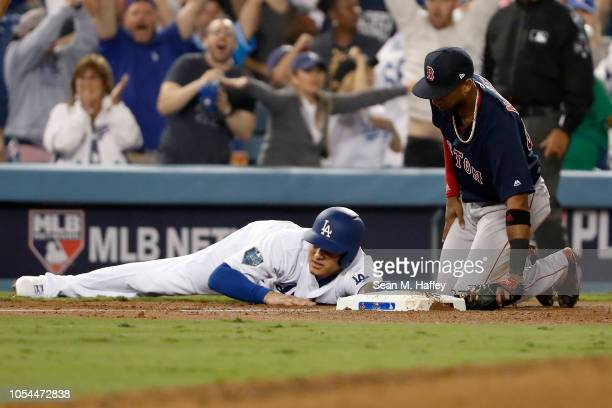 Manny Machado of the Los Angeles Dodgers slides safely into third base as third baseman Eduardo Nunez of the Boston Red Sox looks on in the sixth...