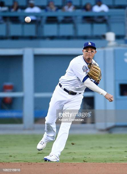 Manny Machado of the Los Angeles Dodgers throws to first base after a fielding error at shortstop during second inning of Game Three of the National...
